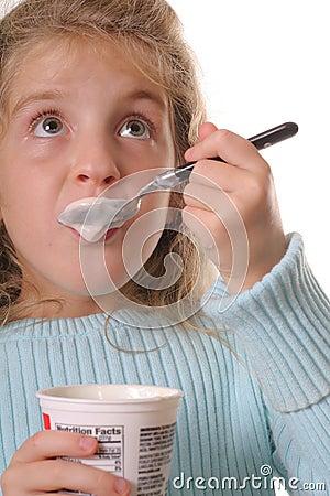 Young girl eating yogurt vertical looking up