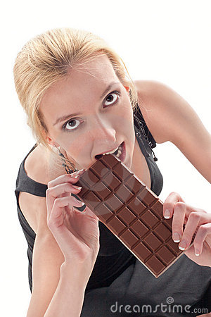 The young girl eats tasty chocolate