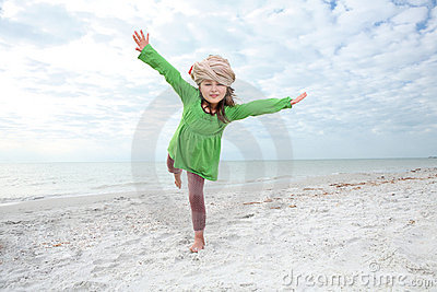 Young girl enjoys summer day at the beach.