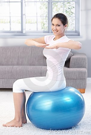 Young girl exercising on fit ball smiling