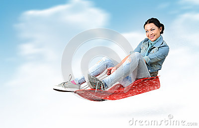 Young girl fly on a sled in the snow