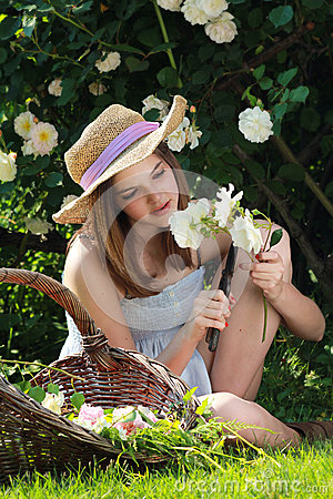 Young girl gardening among white roses