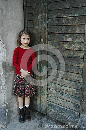 Young girl in gate with sad face, little bit fear,