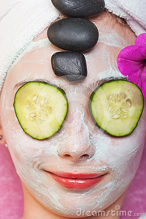 Young girl getting spa treatment with facial mask