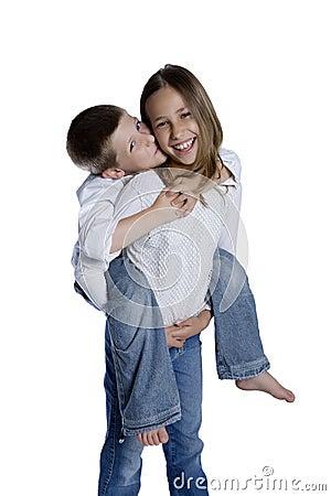 Young girl giving boy piggyback ride, studio shot
