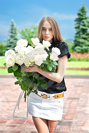 Young girl goes to the park with a large bouquet o