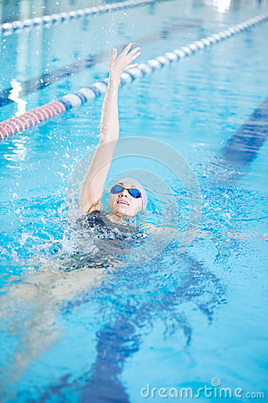 Young girl in goggles swimming back crawl stroke style