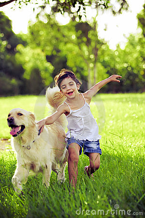 Young girl with golden retriever running