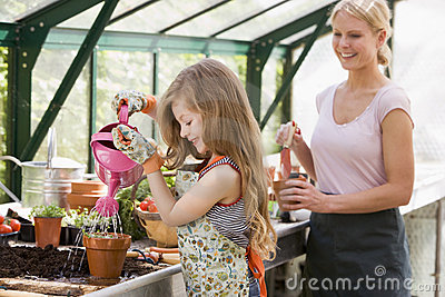 Young girl in greenhouse watering plant with woman