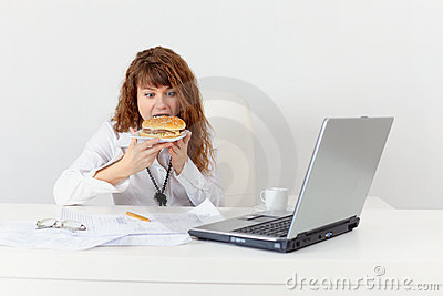 Young girl has hastily dinner sandwich at office