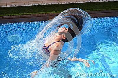 Young girl is having fun in a swimming pool