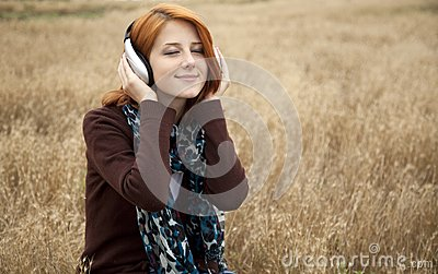 Young girl with headphones at field.