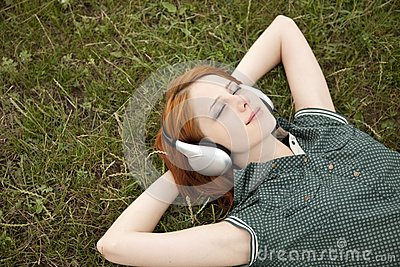 Young girl with headphones lying at green grass.
