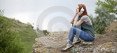 Young girl with headphones at rock