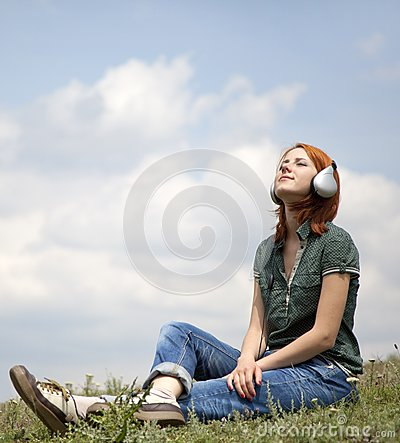 Young girl with headphones sitting at grasss.