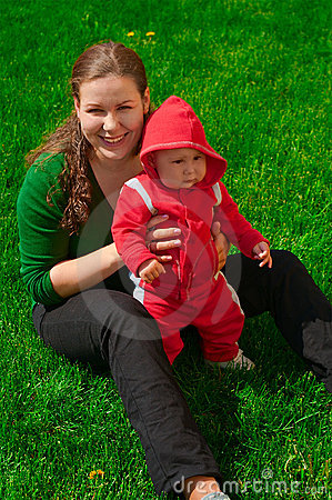 Young girl and her child sit on the green grass
