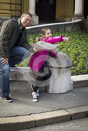 Young girl and her father studying a city map