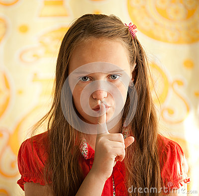 Young girl with her finger over her mouth