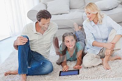 Young girl and her parents using a tablet