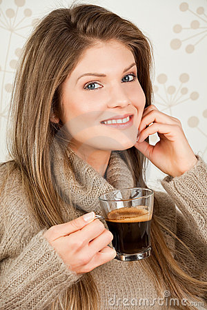Young girl holding a cup of coffee and smiling