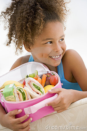 Young girl holding packed lunch in living room