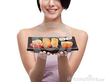 Young girl holding plate of sushi and smiling