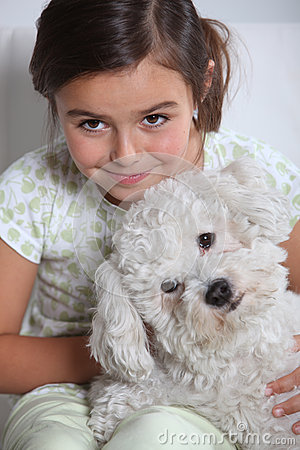 Young girl holding small dog