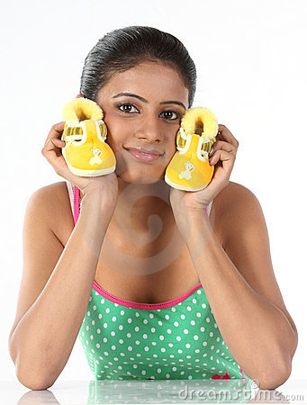 Young girl holds small baby booties in her palm