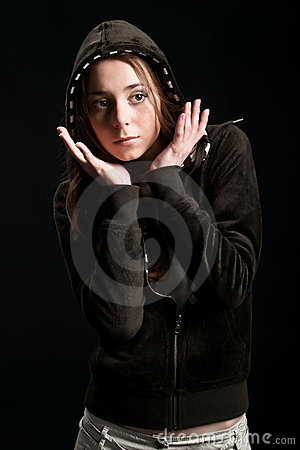 Young girl in hood with hand near face