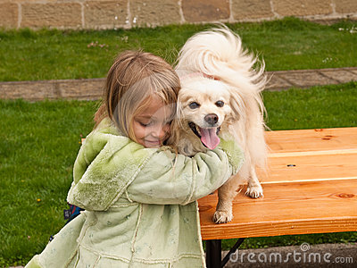 Young girl hugging a little dog