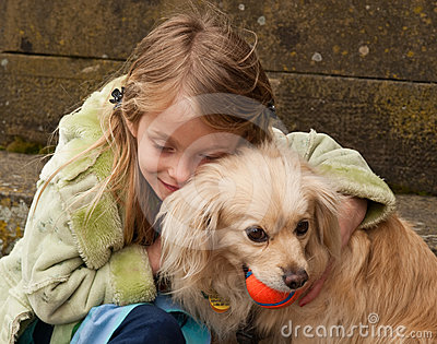 Young girl hugging a little dog with ball