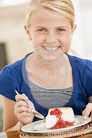 Young girl indoors eating cheesecake
