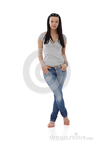 Young girl in jeans and t-shirt standing barefoot