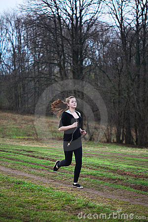 A young girl jogging  in a park