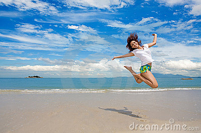 Young girl jumping gracefully at the beach