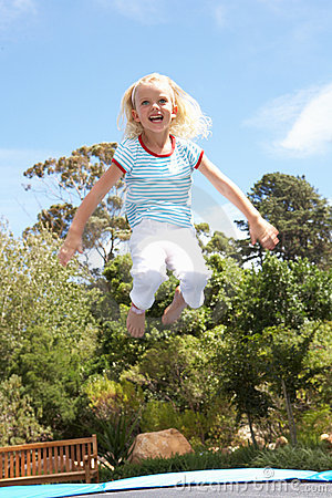 Young Girl Jumping On Trampoline In Garden