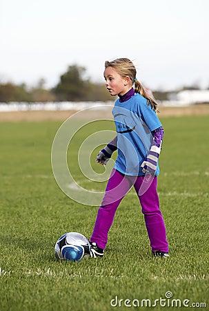 A young girl kicking a soccer ball