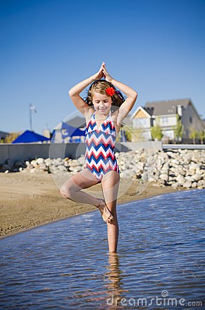 Young girl at the lake in yoga pose