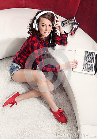 Young girl with laptop listen to music