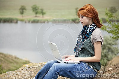 Young girl with laptop at rock near lake
