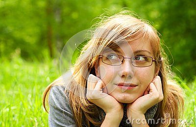 The young girl,  lays on a green grass, in park