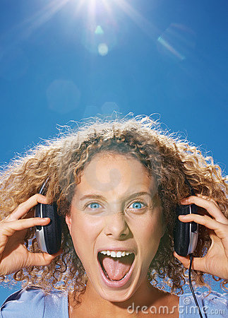 Young girl listening to music and screaming