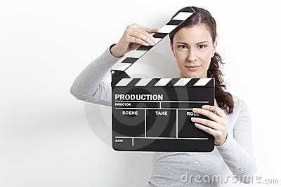 Young girl looking through clapper board