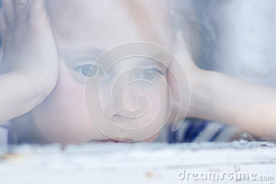 Young girl looking from window