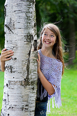 Young girl looks out from the tree