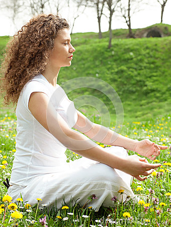 Young girl in lotus pose in the vild flower field