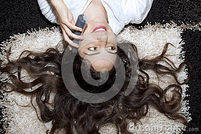 Young girl lying on the carpet with telephone