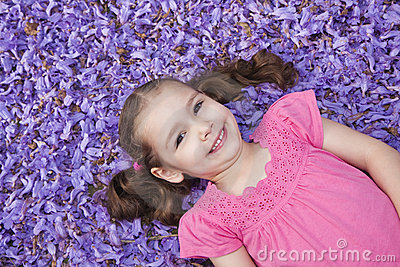 Young girl lying among fallen purple flowers