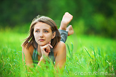 Young girl lying on grass dreaming