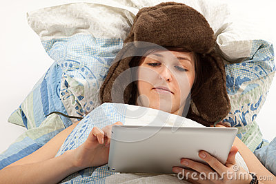 The girl is lying sick in bed and looking into her tablet